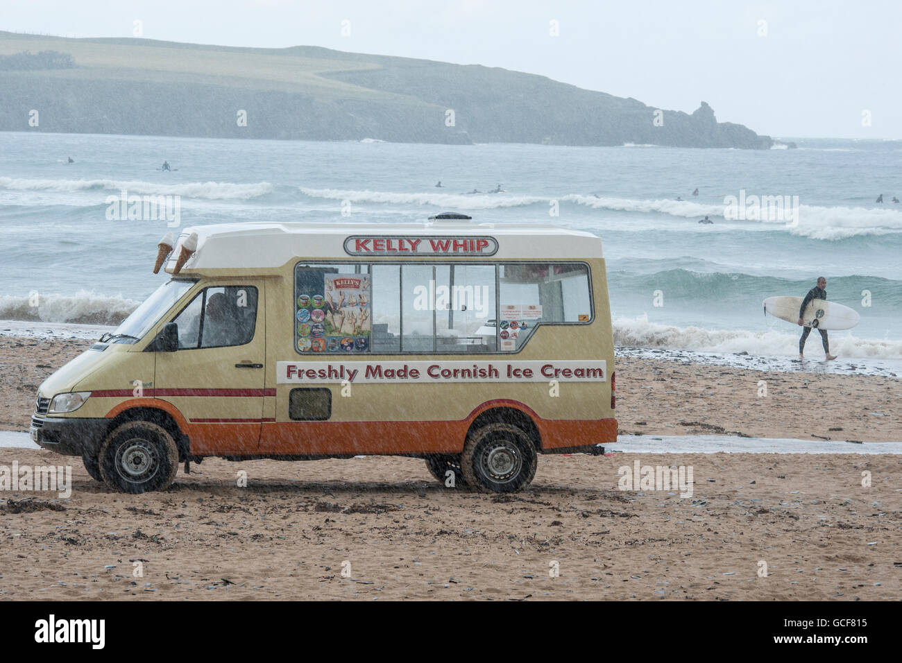 An ice cream van in the pouring rain on a beach in Cornwall - Stock Image
