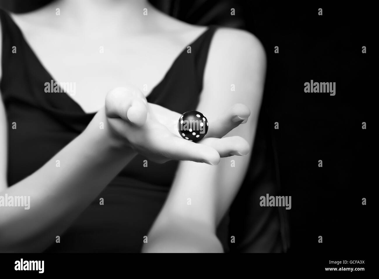 Blurred woman silhouette holding round dice in her hand. Gambling, fortune or randomize concept, black and white - Stock Image