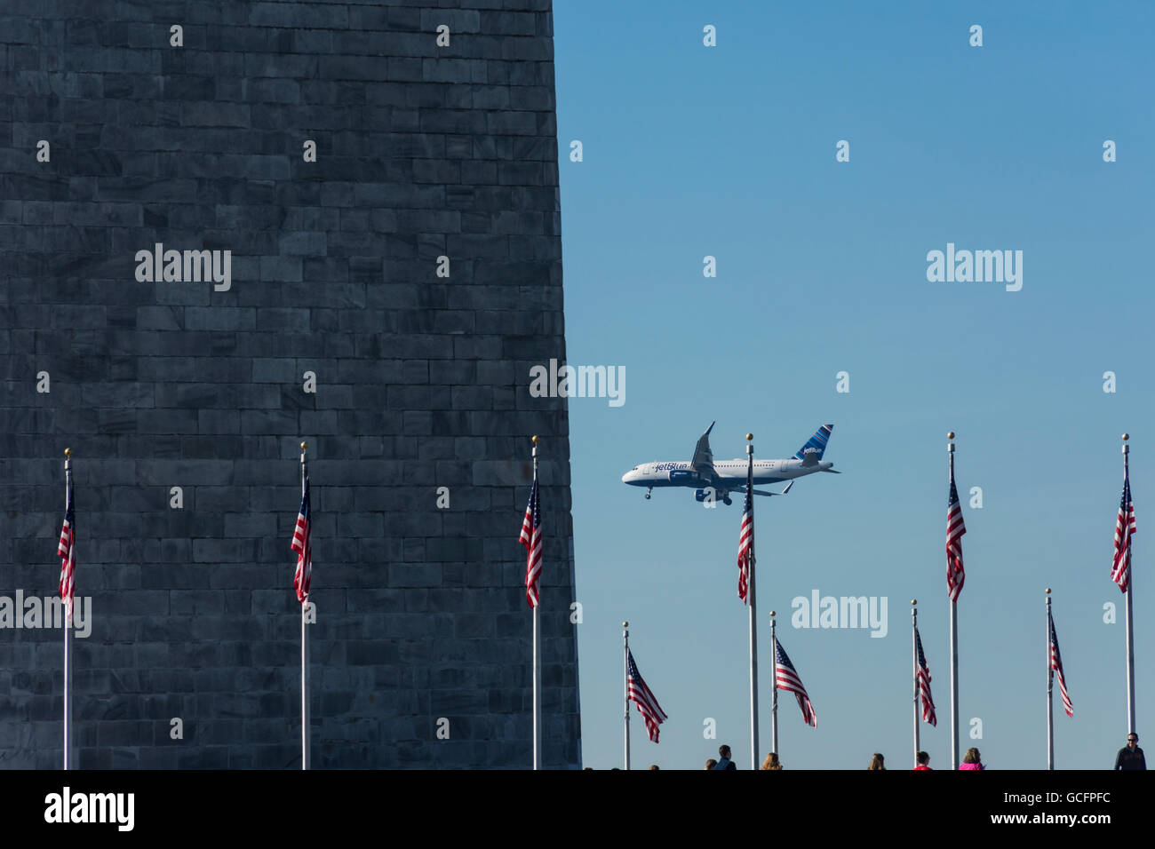 A jetBlue Airbus A320E aircraft with winglets (sharklets) flies by the Washington Monument on way to land at Reagan - Stock Image