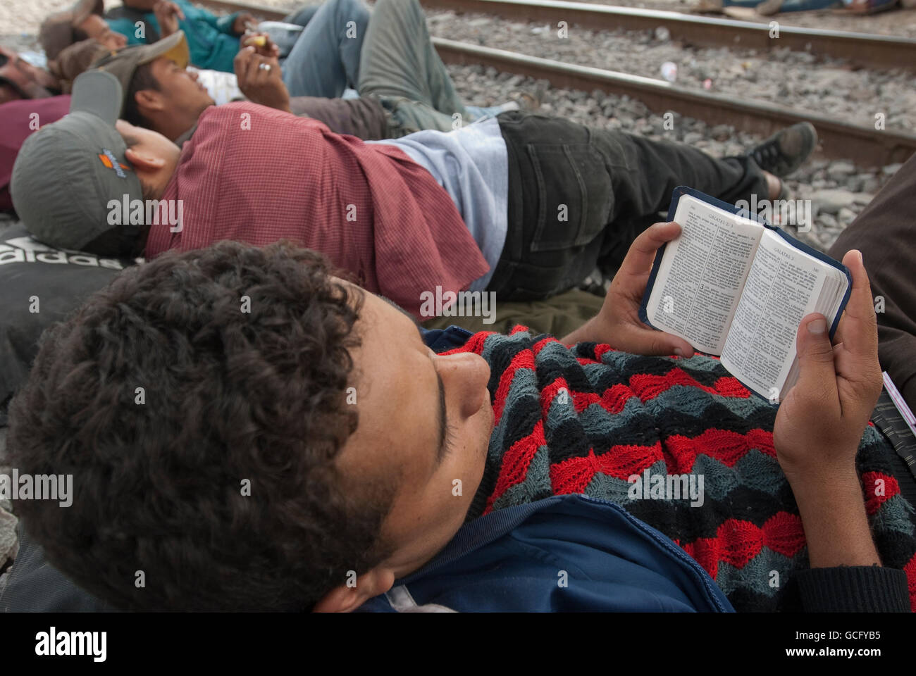 While waiting along the tracks for a northbound train, a young Central American migrant reads his Bible. - Stock Image