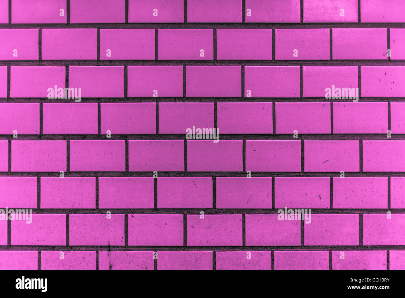 dirty and grainy purple pink or purplish pinkish violet vintage city tiles underground style wall with some splashes - Stock Image