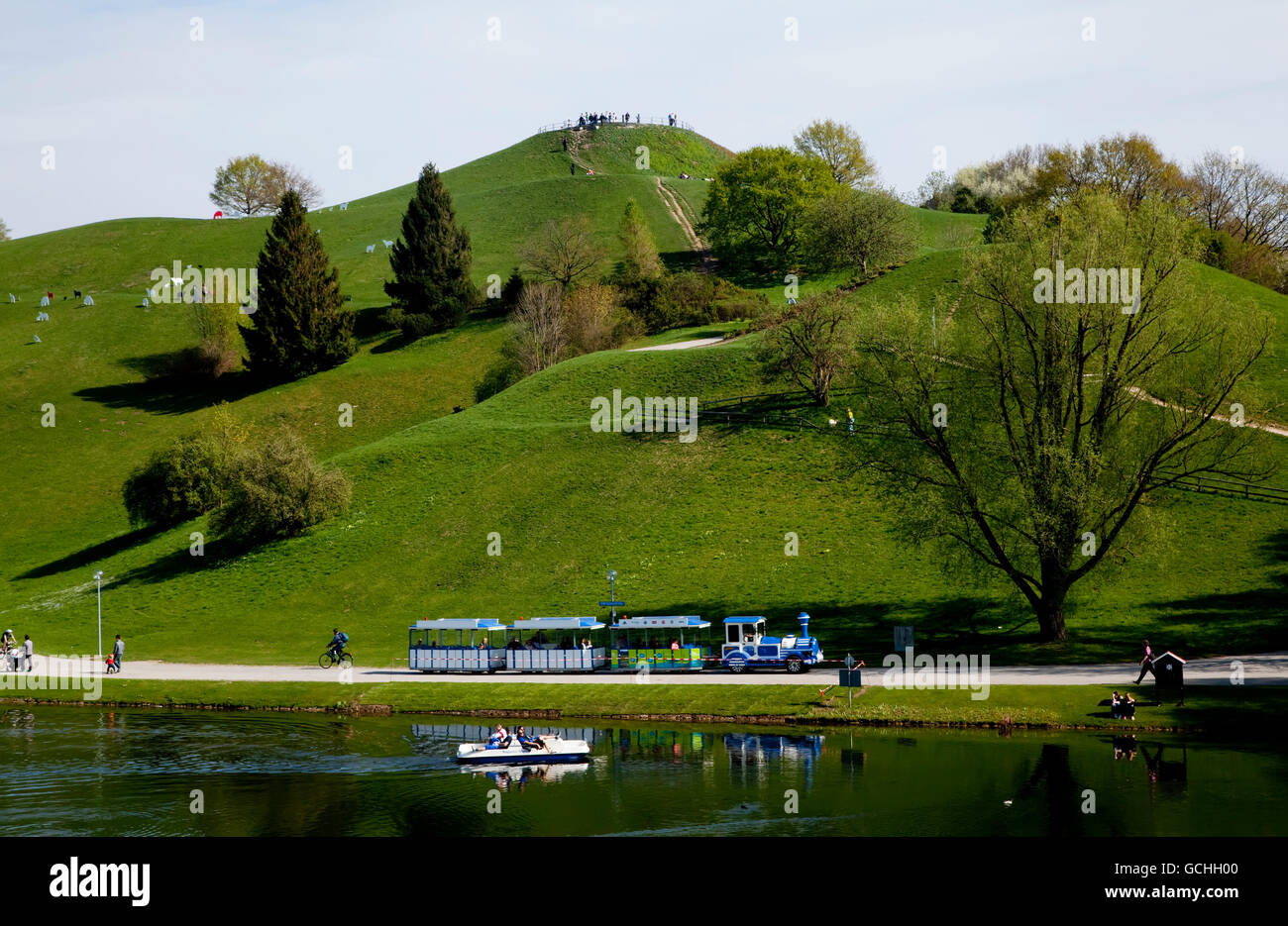 A path leading around and up lush, grassy hills by a lake and Olympiastadion; Munich, Bavaria, Germany - Stock Image