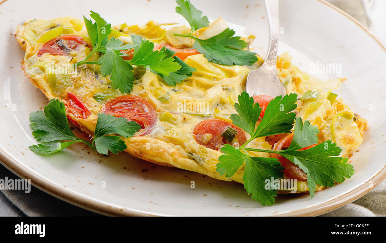 Omelet with vegetables in a white plate. Selective focus - Stock Image