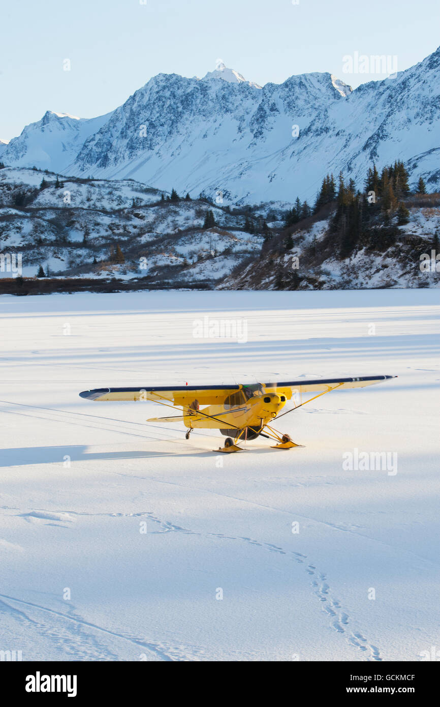 Piper PA-18 Super Cub on skis with the Kenai Mountains in the background, Southcentral Alaska. - Stock Image