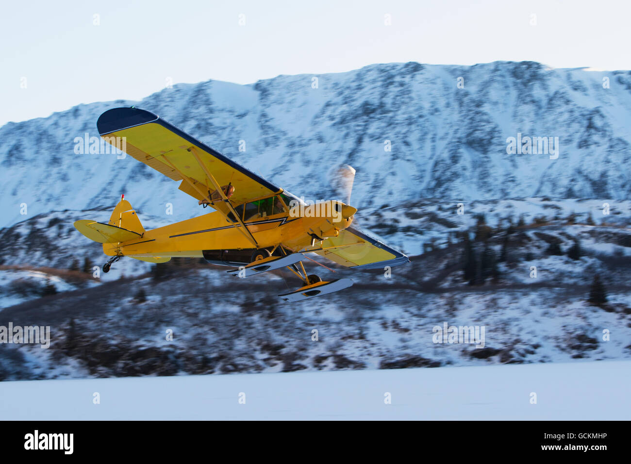 Piper PA-18 Super Cub on skis takes off with the Kenai Mountains in the background, Southcentral Alaska. - Stock Image