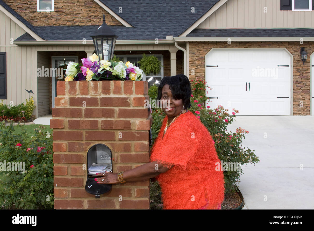 smiling black senior adult female homeowner getting her mail - Stock Image