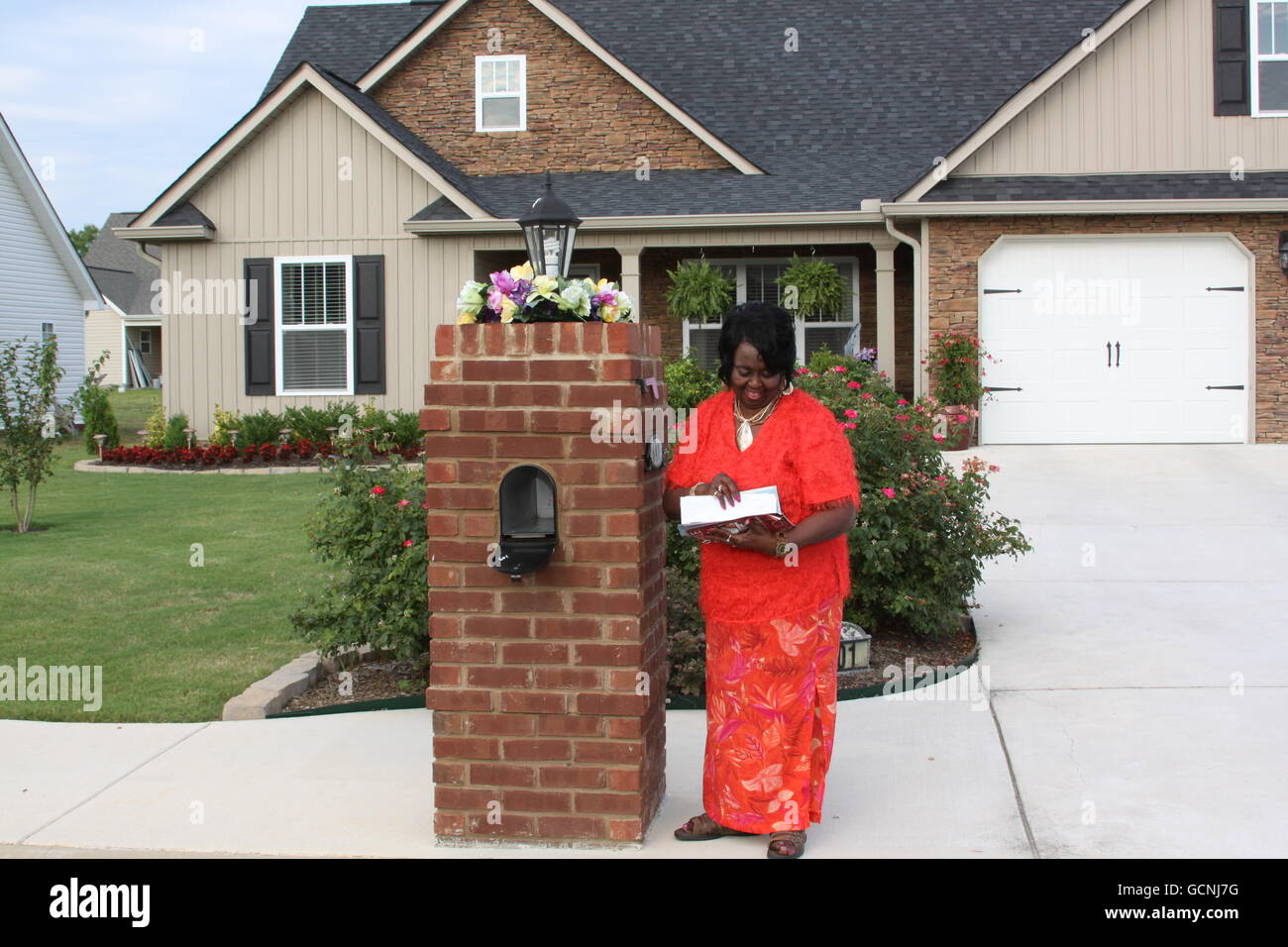 black female senior adult homeowner getting her mail - Stock Image