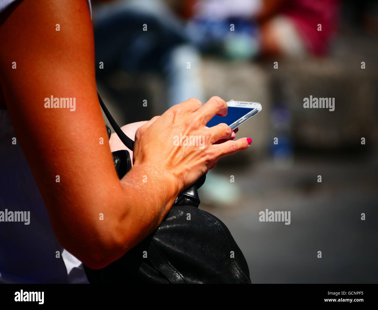 Lady Woman checking SMS email on smartphone iPhone - Stock Image