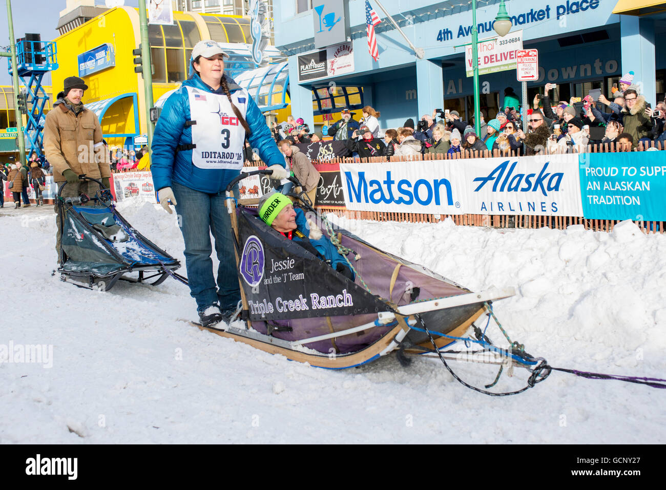 Jessie Royer and team leave the ceremonial start line with an Iditarider during the 2016 Iditarod - Stock Image