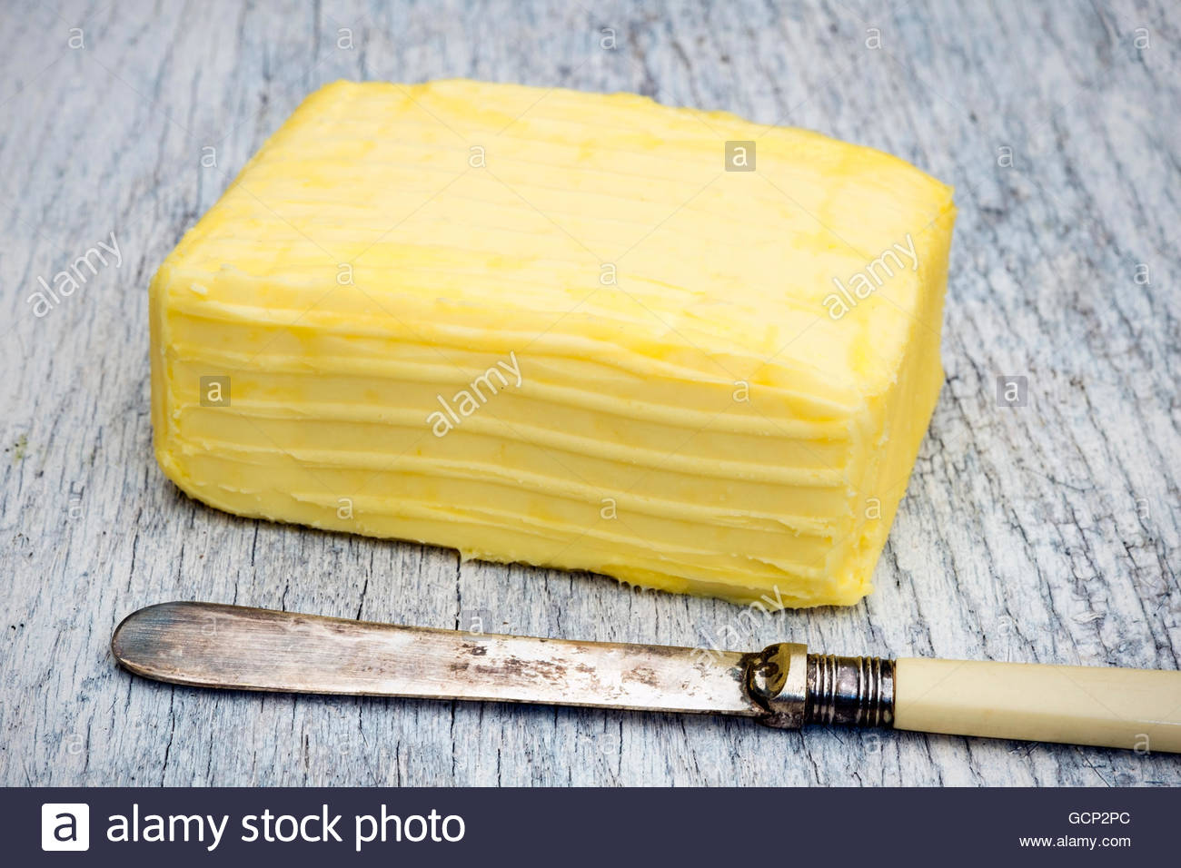 Block of butter & knife outdoors on a picnic table. - Stock Image