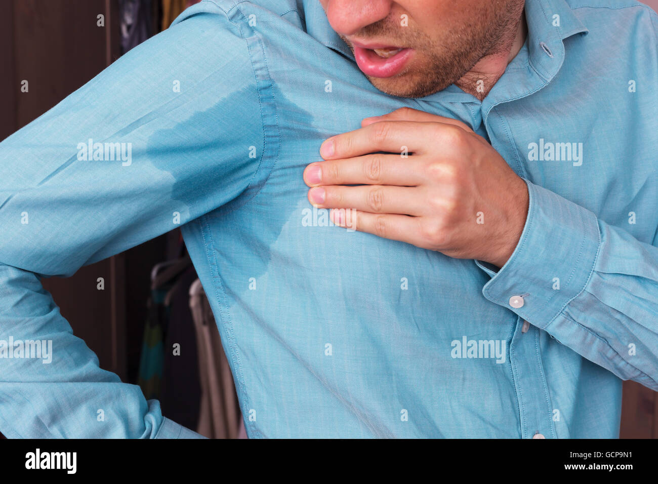 Sweaty spot on the shirt because of the heat, worries and diffidence - Stock Image