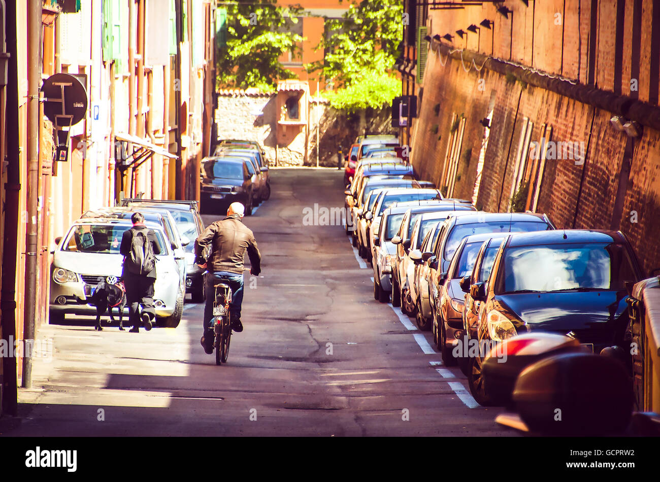 Bologna, Italy bald man cross street with bicycle alongside a row of parked cars - Stock Image