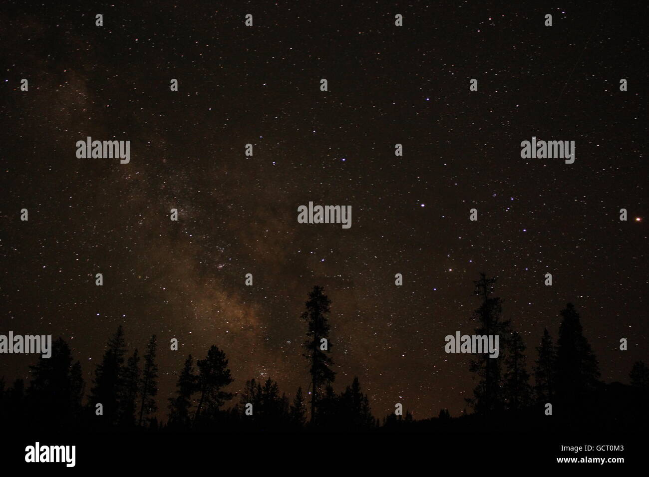 Stars, galaxies and space dust illuminate the night sky in the mountains. - Stock Image