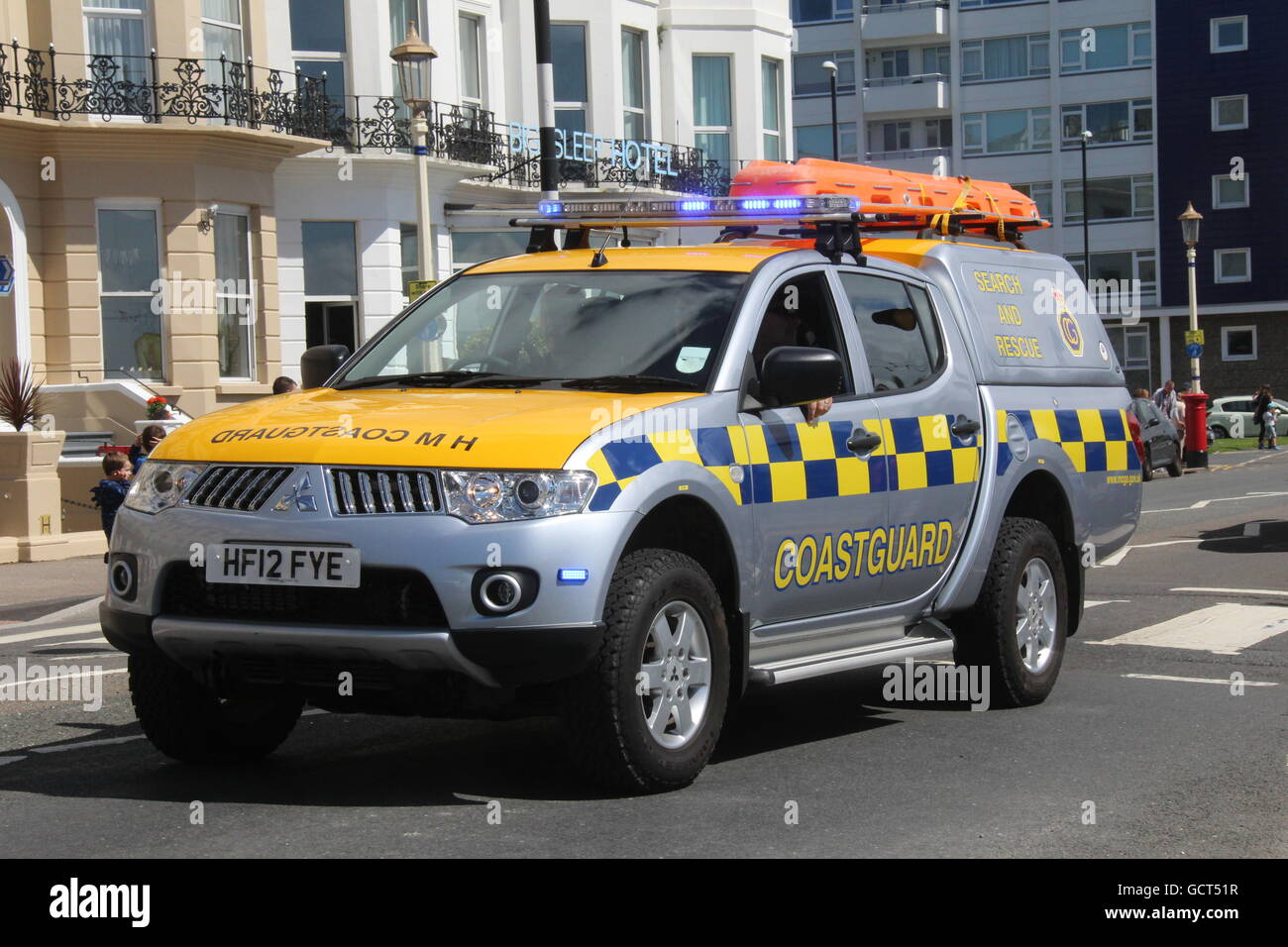 A SUNNY NEARSIDE VIEW OF A H. M. COASTGUARD 4-WHEEL DRIVE VEHICLE WITH BLUE LIGHTS FLASHING TRAVELLING ALONG A ROAD - Stock Image