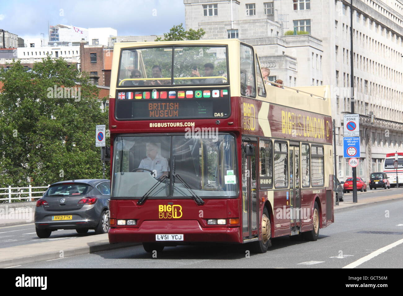 a sunny nearside view of a big bus London sightseeing bus - Stock Image