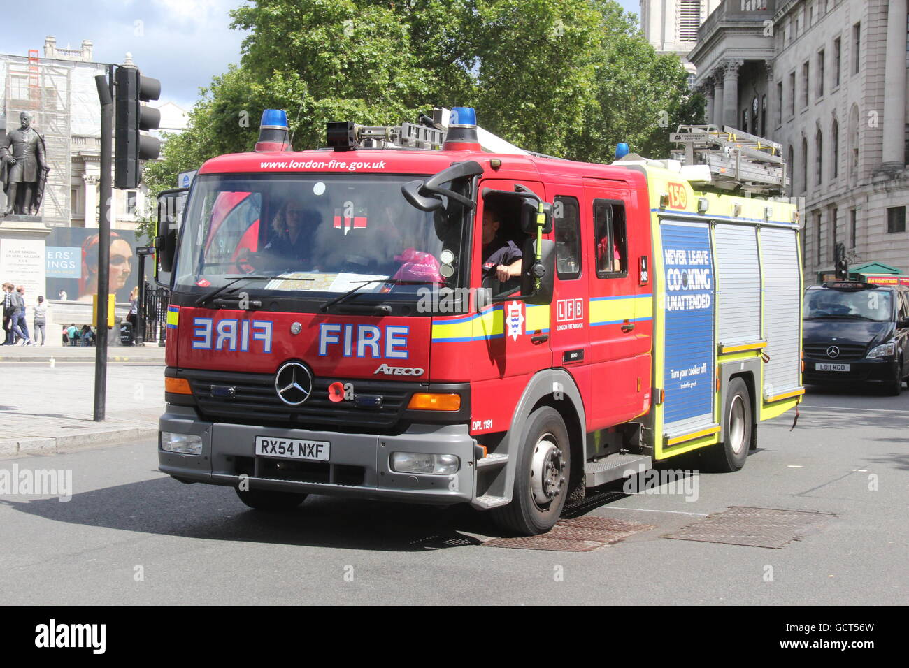 A SUNNY NEARSIDE LANDSCAPE VIEW OF A LONDON FIRE BRIGADE MERCEDES FIRE TRUCK PASSING THROUGH TRAFALGER SQUARE - Stock Image