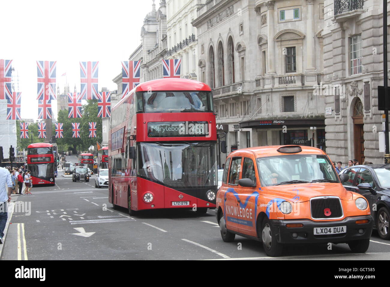 A LONDON TAXI ON ADVERT LIVERY AND A RED NEW ROUTEMASTER LONDON BUS IN CENTRAL LONDON - Stock Image