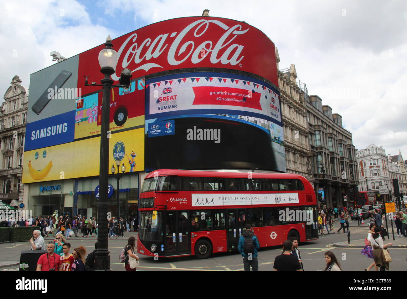 PICADILLY CIRCUS IN LONDON WITH RED LONDON NEW ROUTEMASTER BUS AND ADVERTISEMENT BOARDS - Stock Image