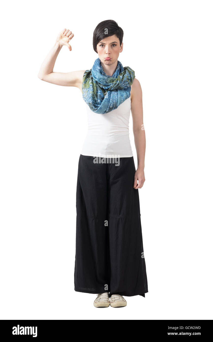 Grumpy trendy woman in wide-leg pants and neckerchief with thumbs down gesture. Full body length portrait isolated - Stock Image