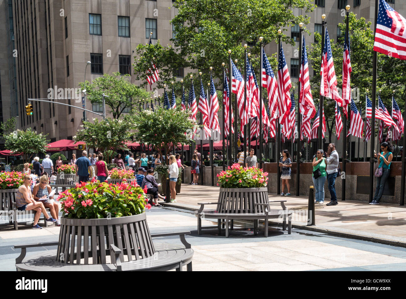 Tourists on Round benches and American Flags at Rockefeller Center ...