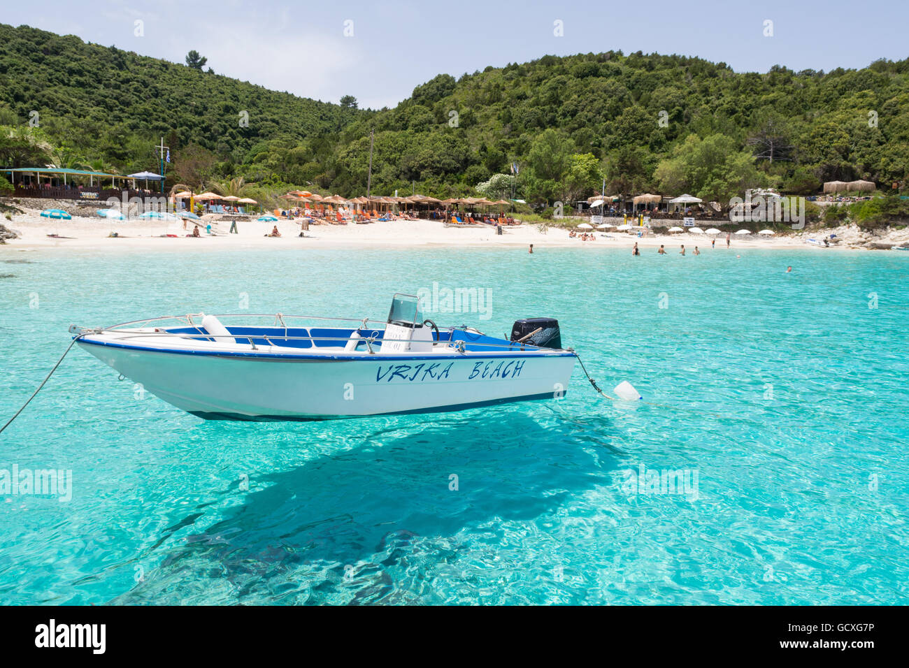 Vrika Beach, AntiPaxos, Greece - small boat moored in the clear turquoise waters of Vrika Bay looking towards beach - Stock Image