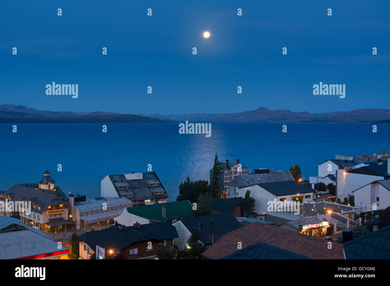 The moon rising over a lake from above the town roof tops showing some yellow city lights against the blue scene; - Stock Image