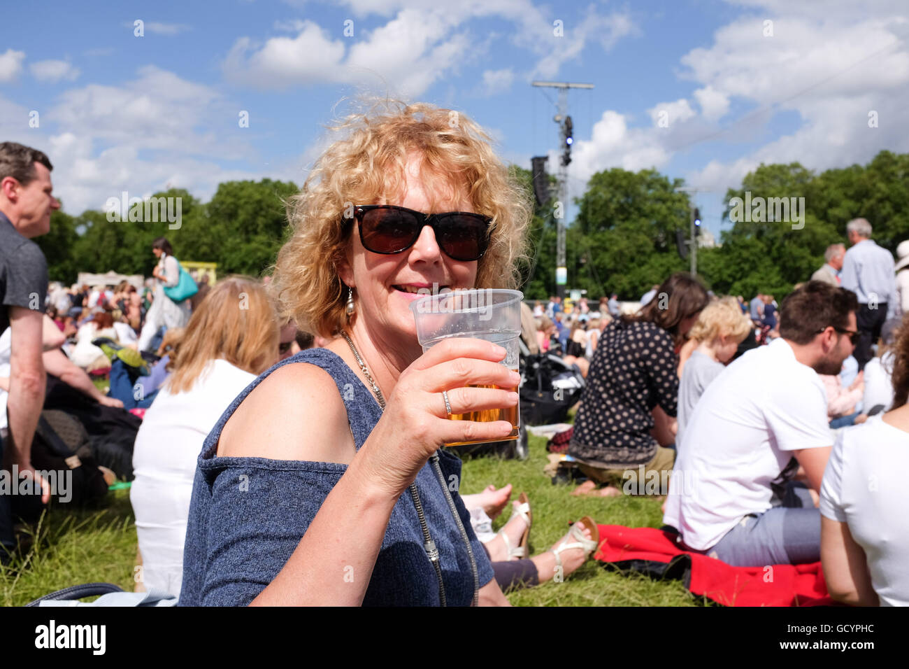 Woman enjoying a pint of beer outside in a plastic glass in summer UK - Stock Image