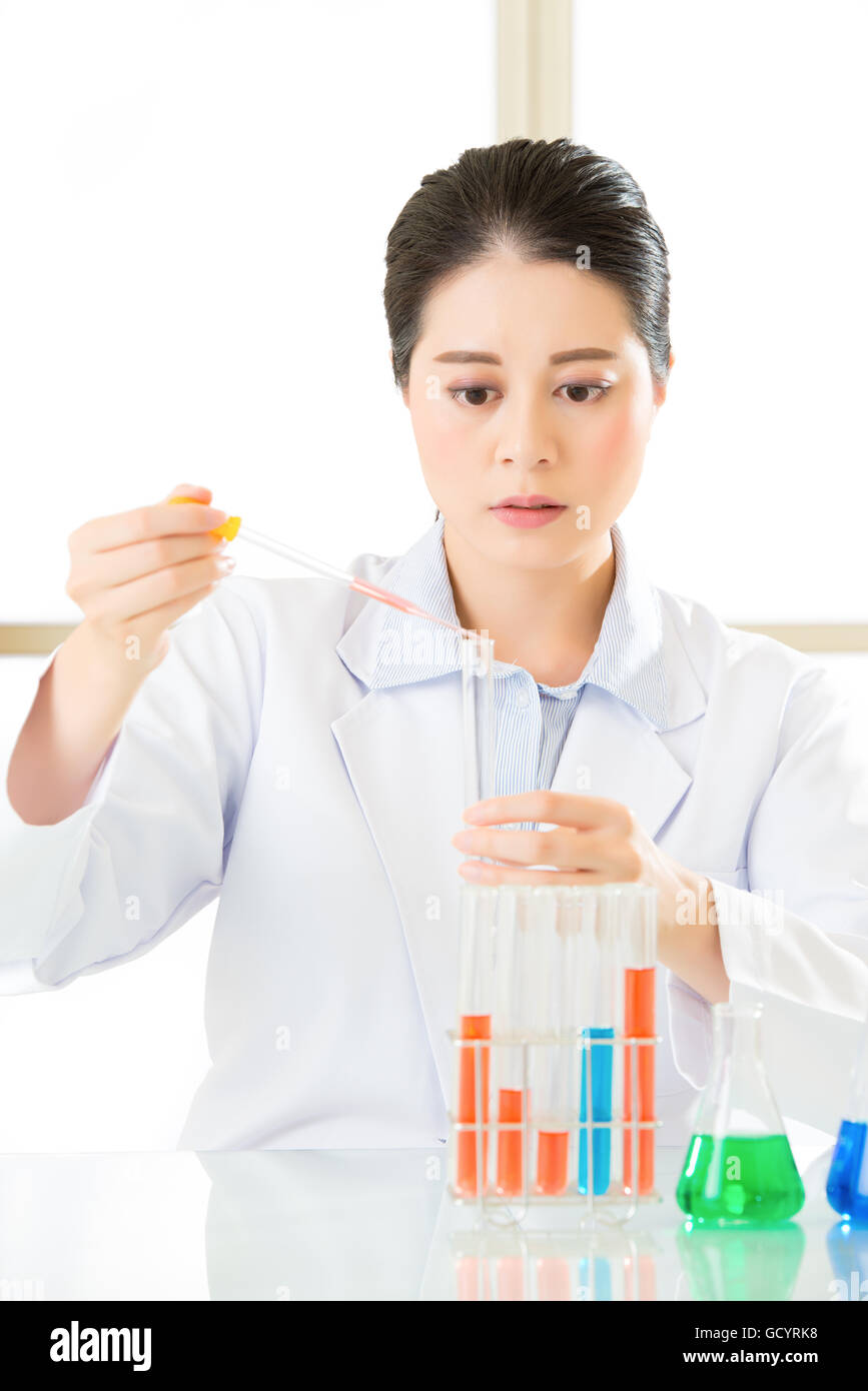 Asian female forensic scientist working on chemicals in laboratory - Stock Image