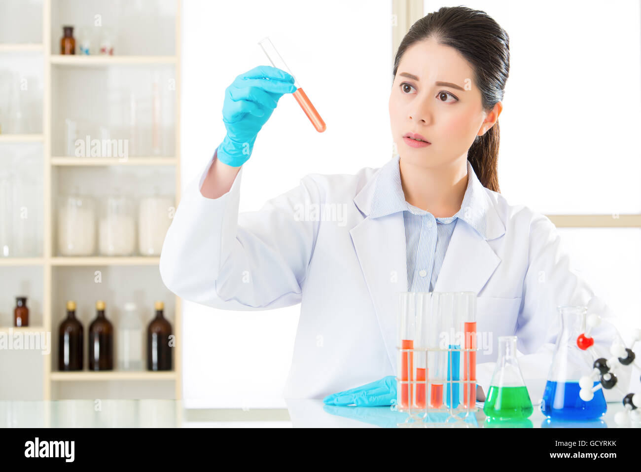 Asian female forensic scientist braving new medical frontiers on chemicals in laboratory - Stock Image