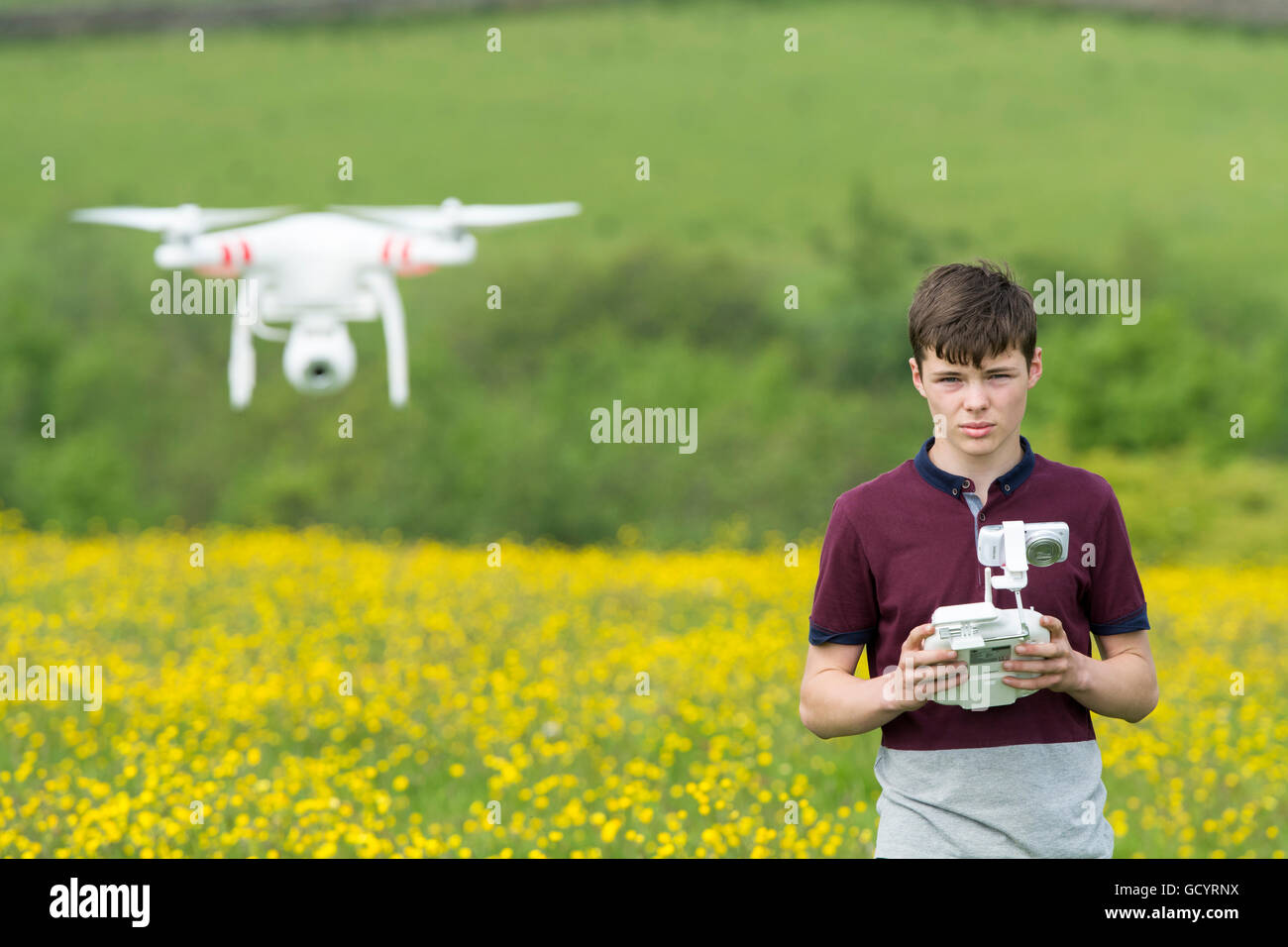 Teenage boy operating a quadcopter drone in countryside, UK. - Stock Image