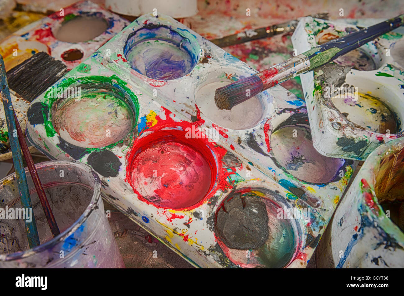 discarded left behind dirty paint brushes in butlers sink needing a serious clean and polish after messy art students - Stock Image