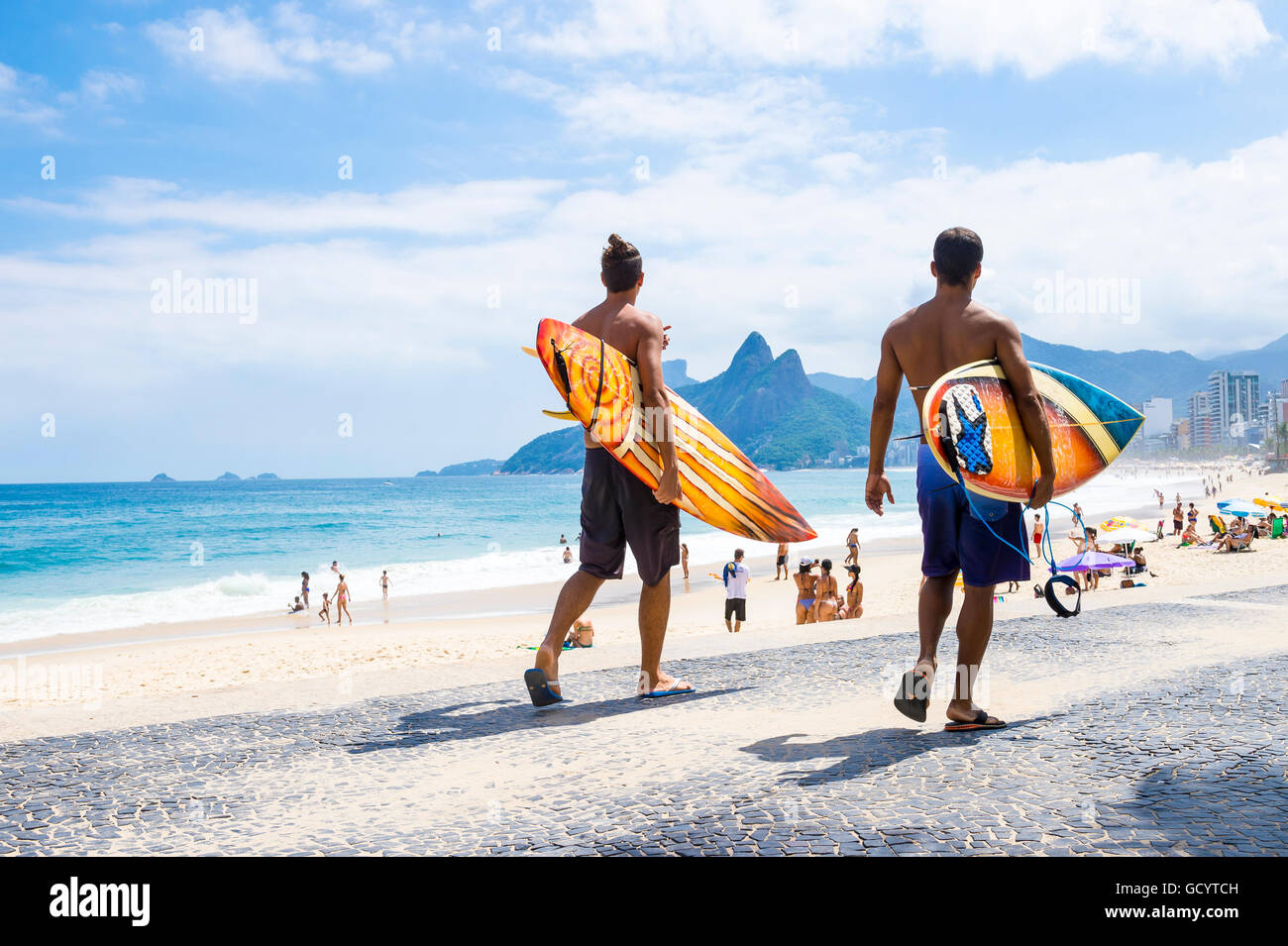 RIO DE JANEIRO - APRIL 3, 2016: Young carioca Brazilians walk with surfboards from Arpoador, the popular surf point. - Stock Image