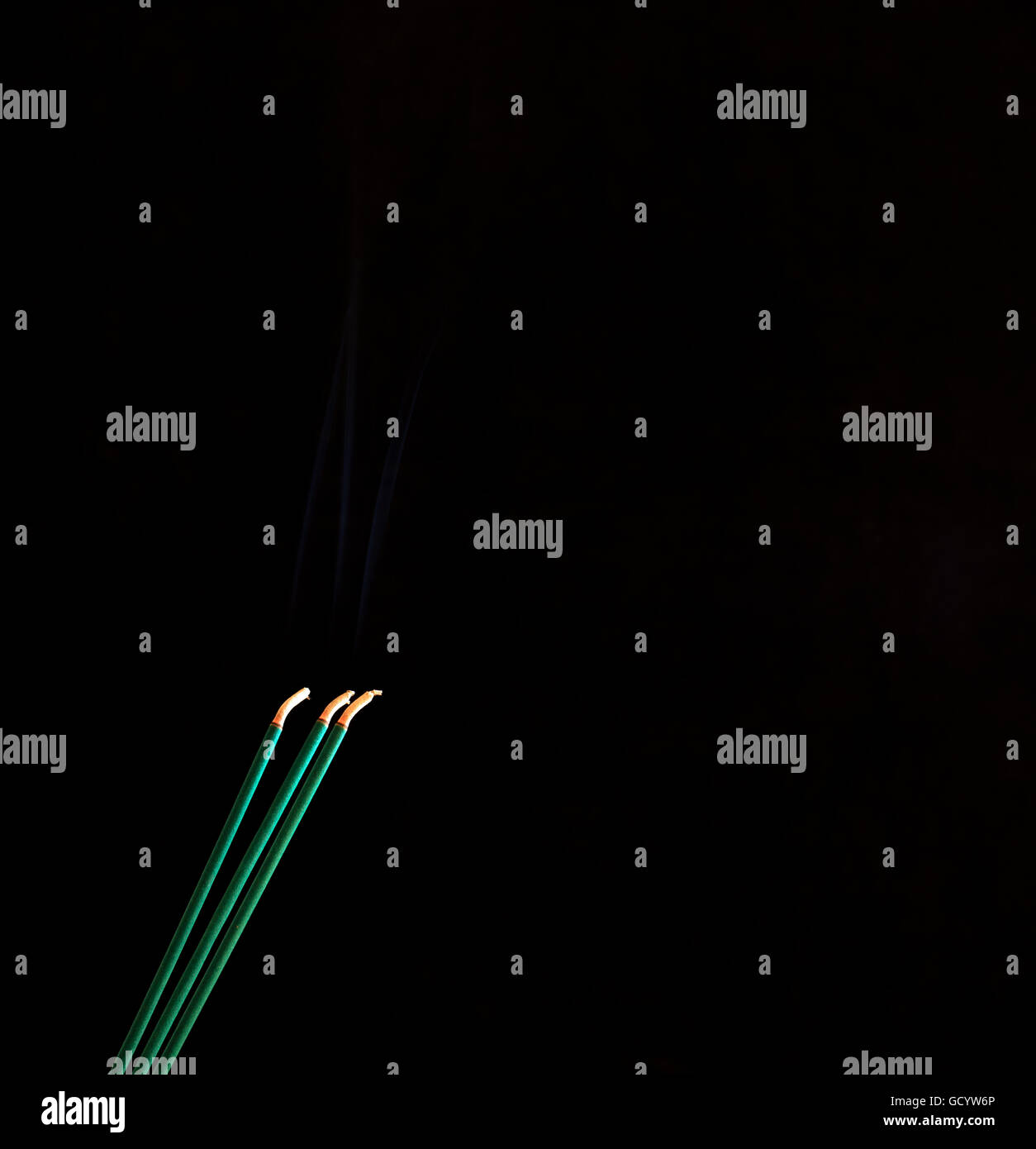 tree green incense sticks dispersing a delightful aroma on a black background - Stock Image