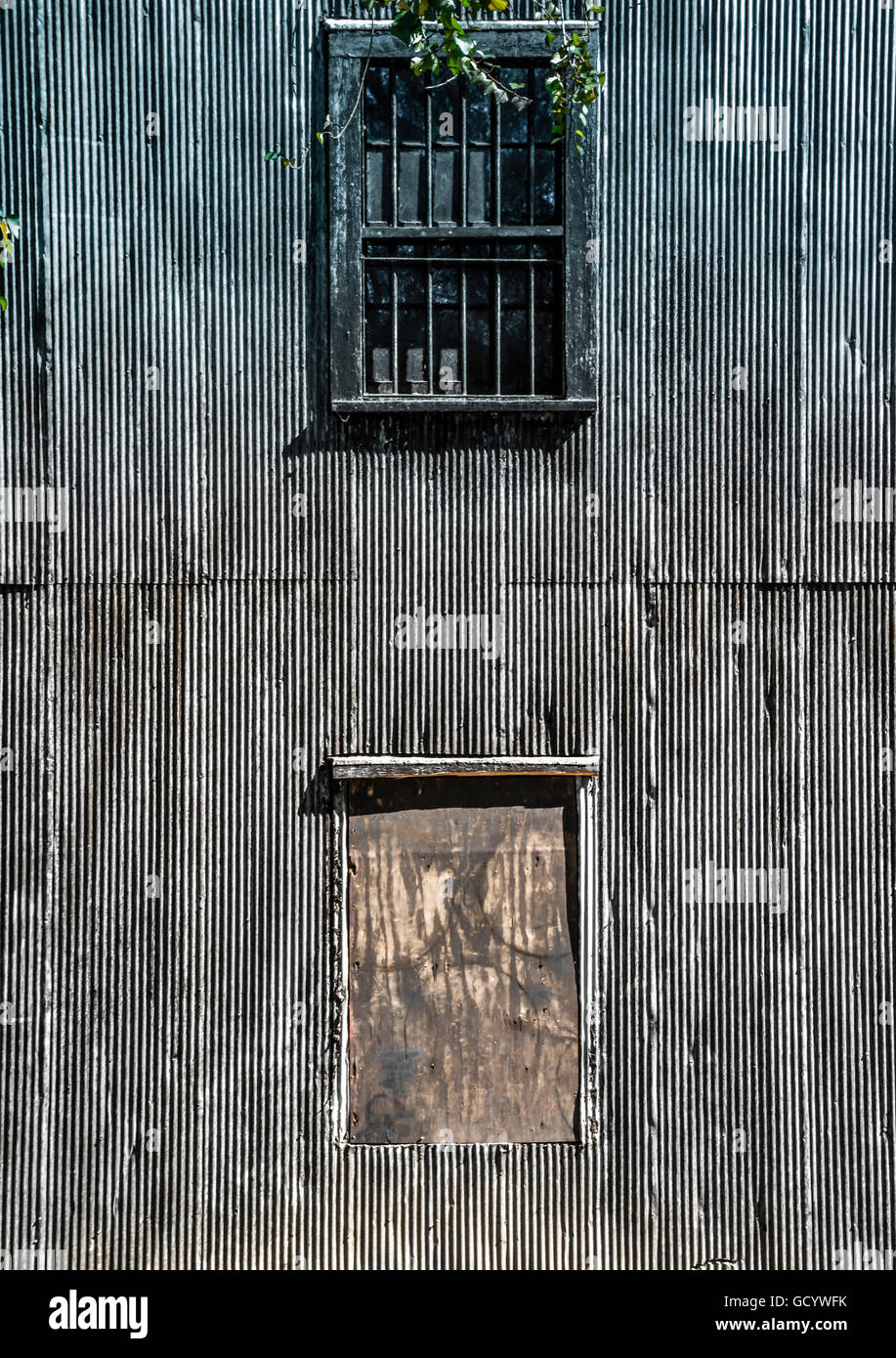 Close up of an old dark, large corrugated metal building with boarded up windows and bars looks abandoned, mysterious - Stock Image