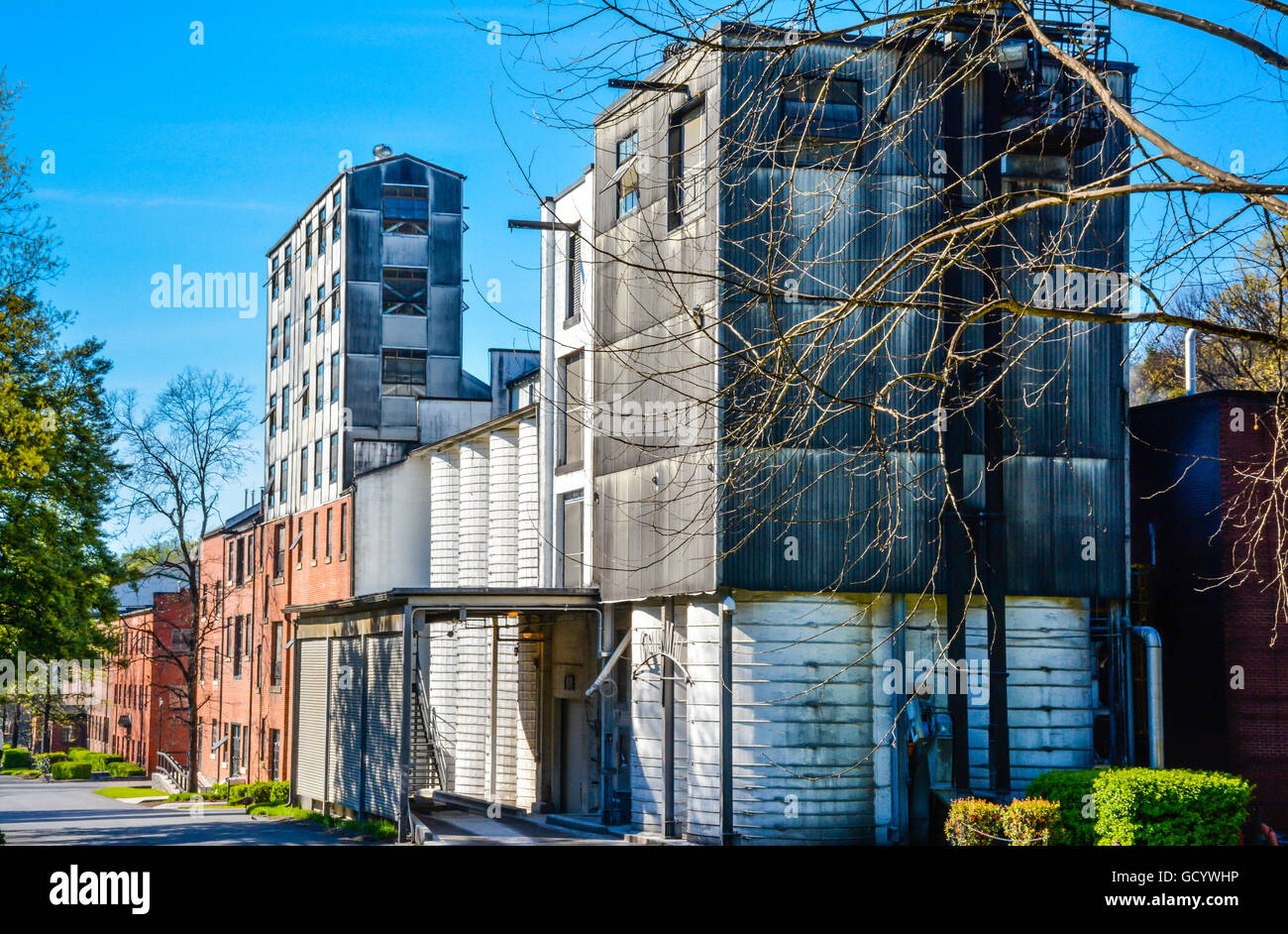 Old blackened metal buildings with old grain mill structures on the grounds of the Jack Daniel's Distillery - Stock Image