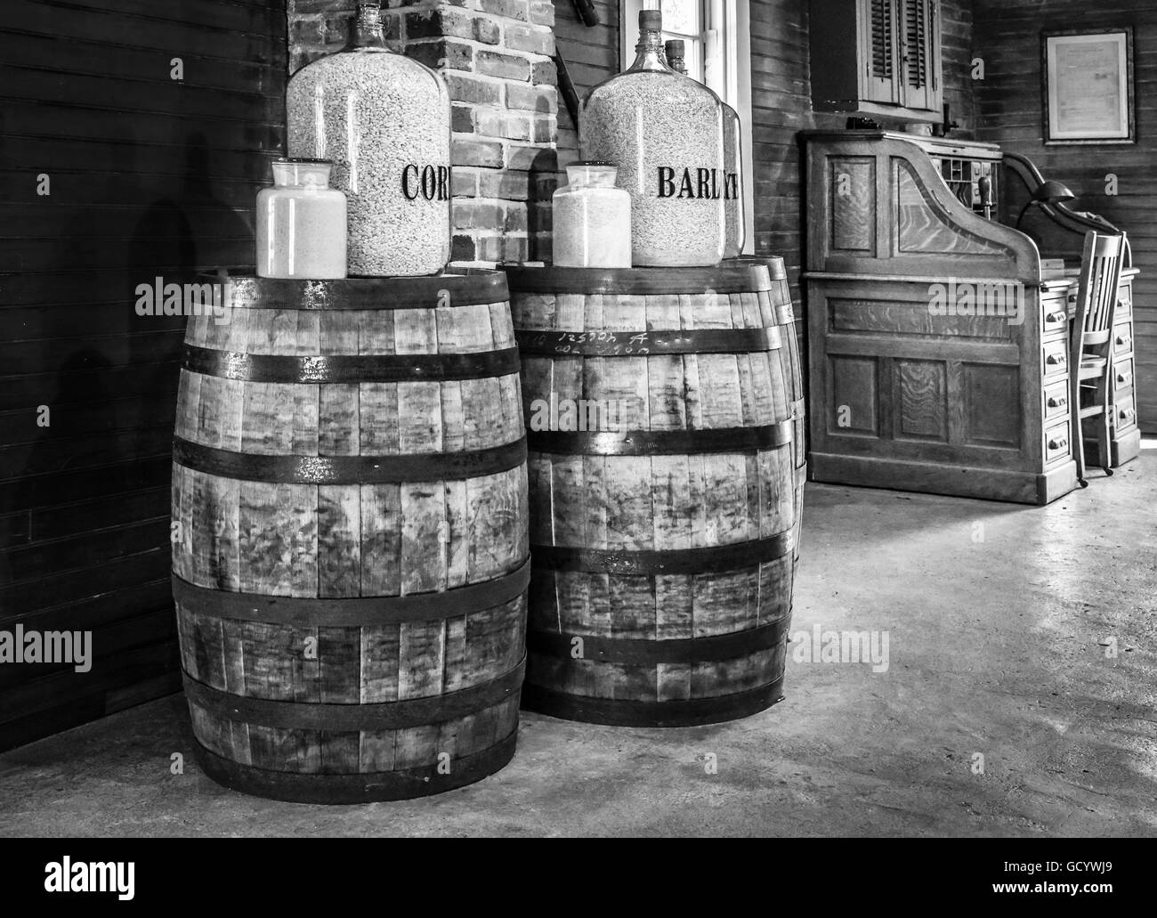 Corn & Barley jugs atop two authentic, aged oak barrels with metal bands and secretary furniture within a vintage - Stock Image