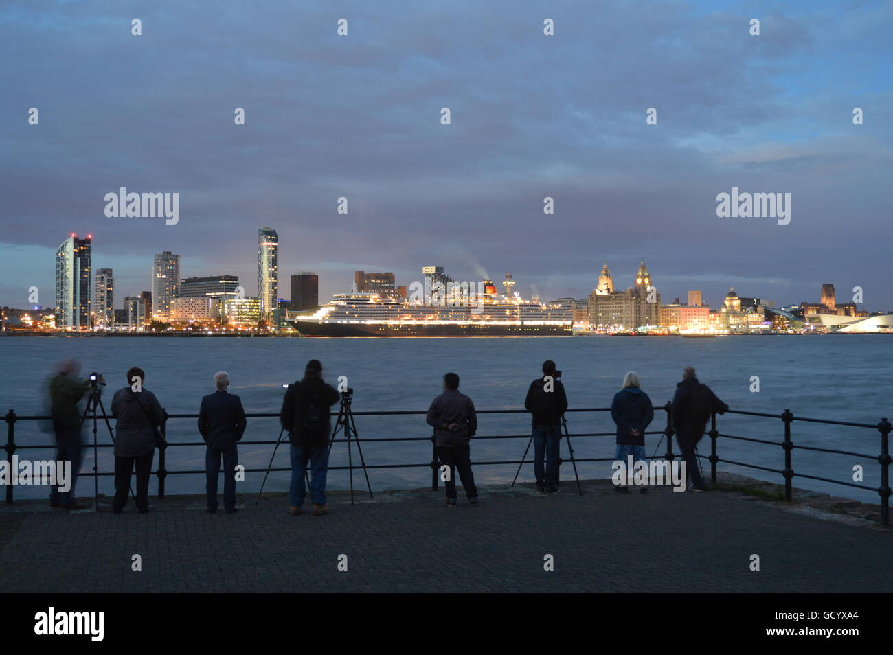 Queen Elizabeth cruise ship berthed in Liverpool at dusk, viewed from Seacombe,Wallasey on the Wirral. - Stock Image
