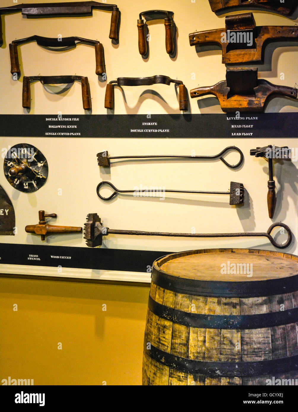 Exhibition of whiskey making tools on display with an oak barrel during tour of the Jack Daniel's Distillery - Stock Image