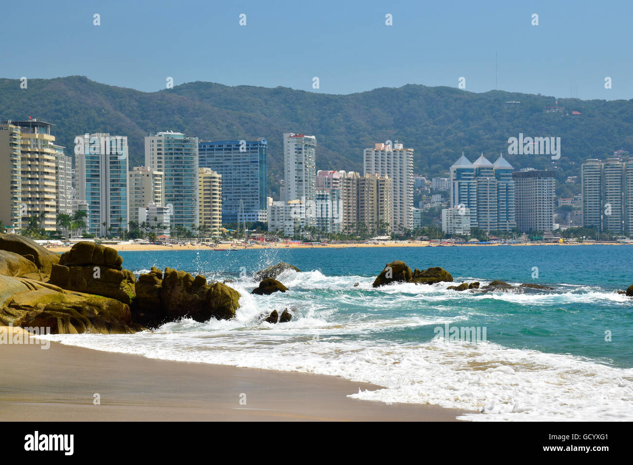 Pacific Ocean in Acapulco Bay and skyline of Acapulco, Mexico - Stock Image
