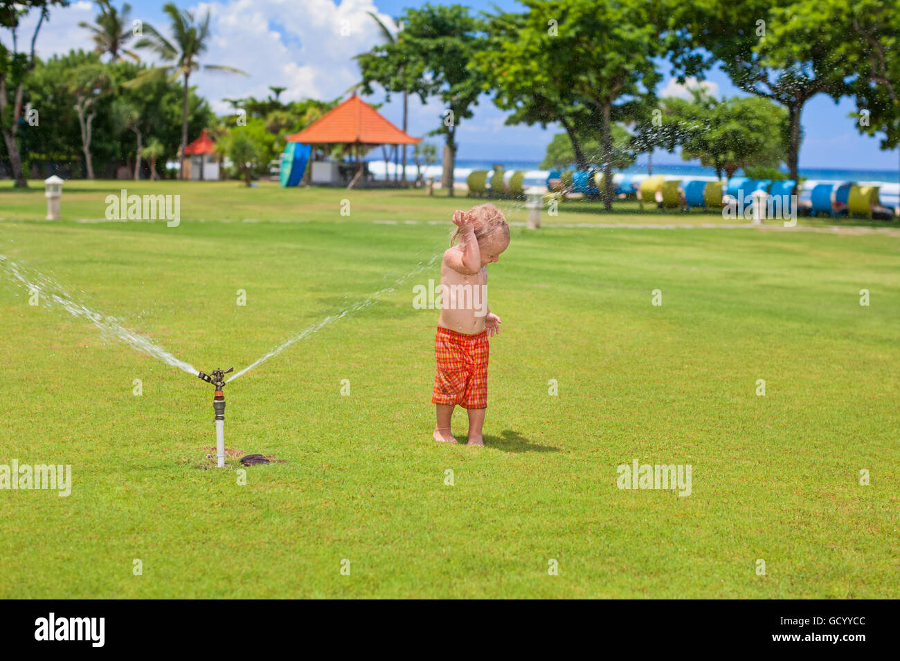 Happy baby boy play with sprinkler spray, swim and splash with fun under water drops on green grass lawn. Stock Photo