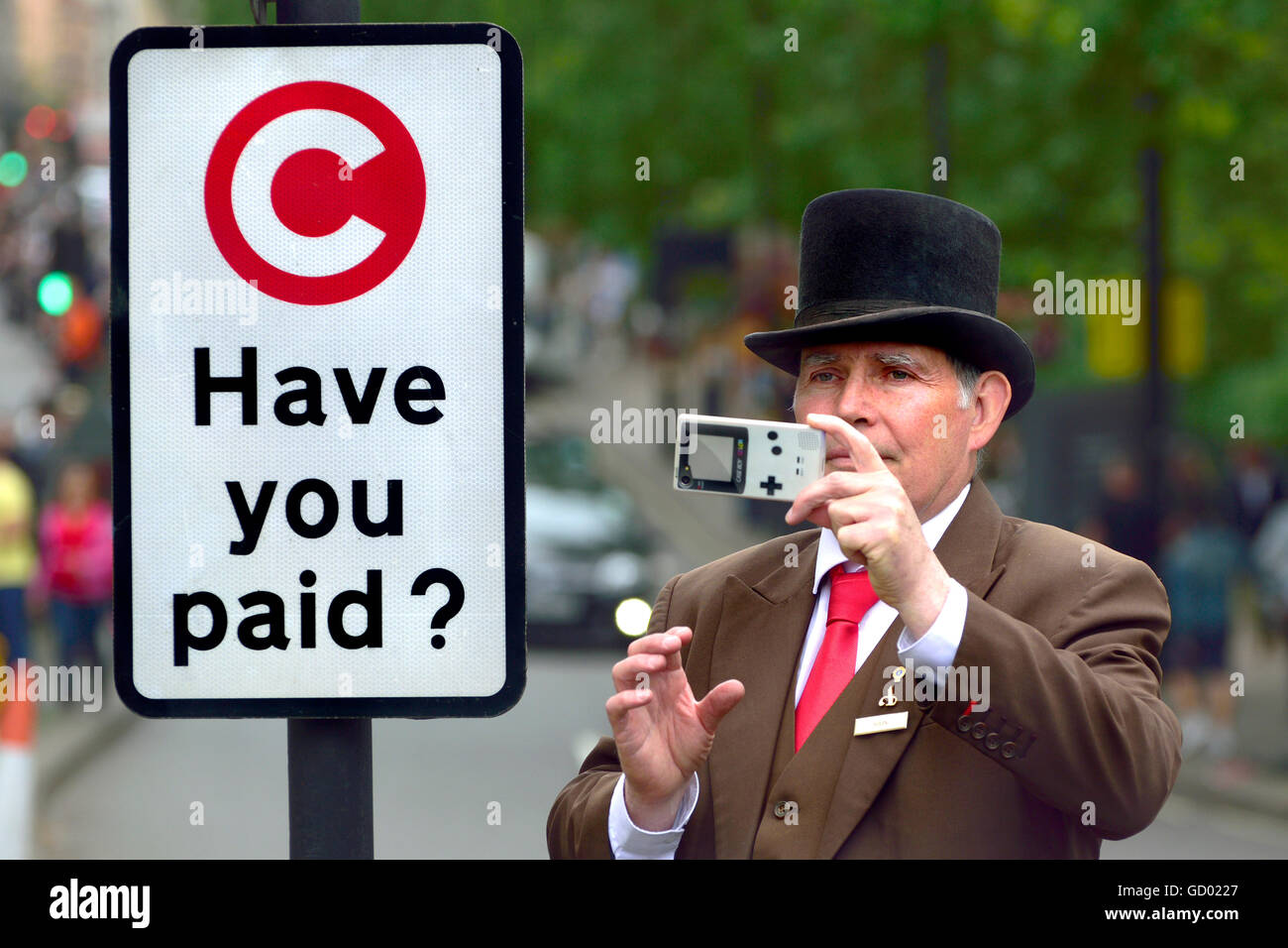 London, England, UK. Hotel doorman taking a photo of a demonstration in Park Lane, next to a Congestion Charge sign - Stock Image