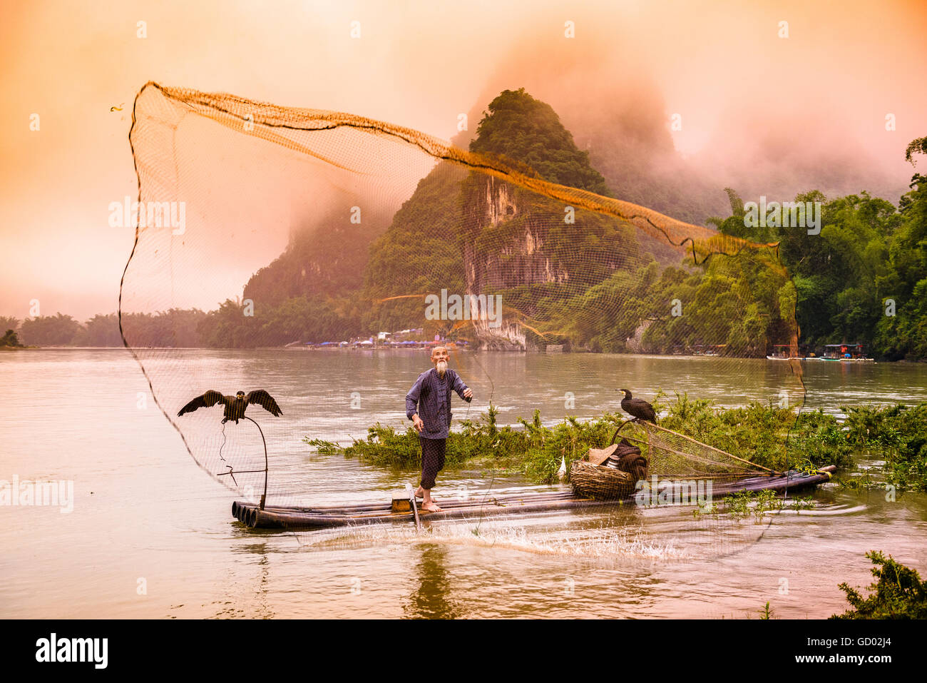 Traditional Chinese cormorant fisherman casts a net on the Li River in Yangshuo, China. - Stock Image