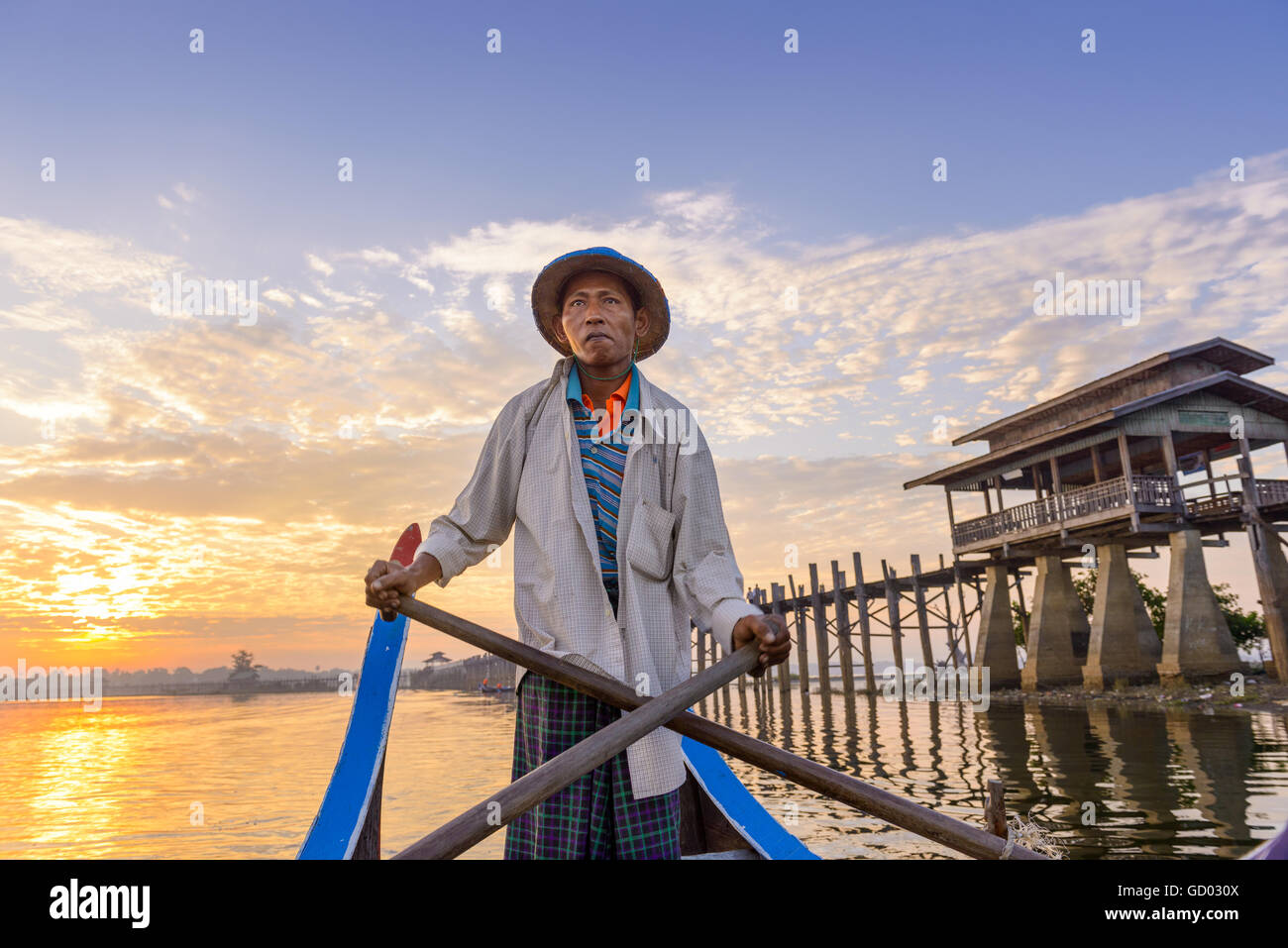 MANDALAY, MYANMAR - OCTOBER 28, 2015: A Gondolier paddles on Taungthaman Lake at U-Bein Bridge. - Stock Image