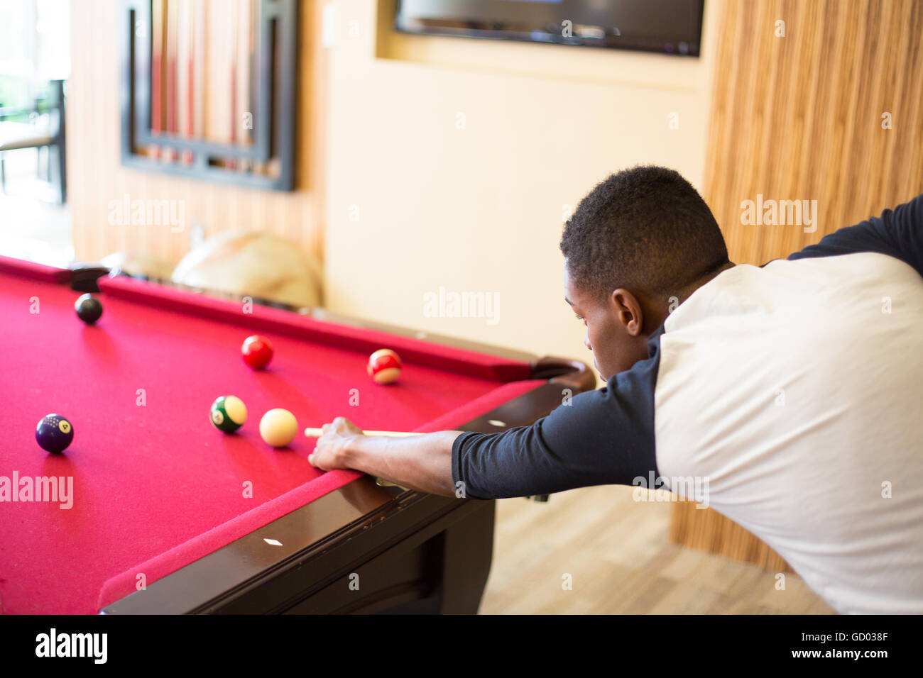 Closeup portrait, young man hanging out, playing billiards at red pool table, isolated indoors background - Stock Image