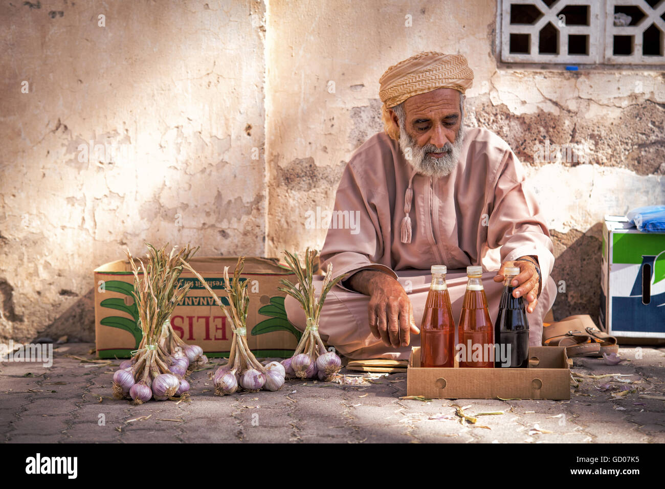 NIZWA, OMAN - APRIL 24 2015:Omani old man selling honey and garlic at the traditional market or souq in Nizwa, Oman - Stock Image