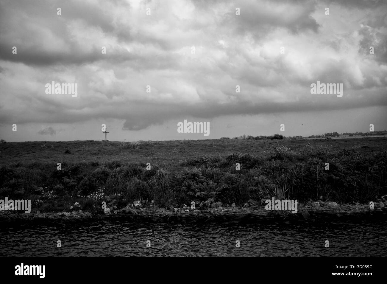 A lone cross on the bank of the Norfolk Broads set against a stormy sky - Stock Image