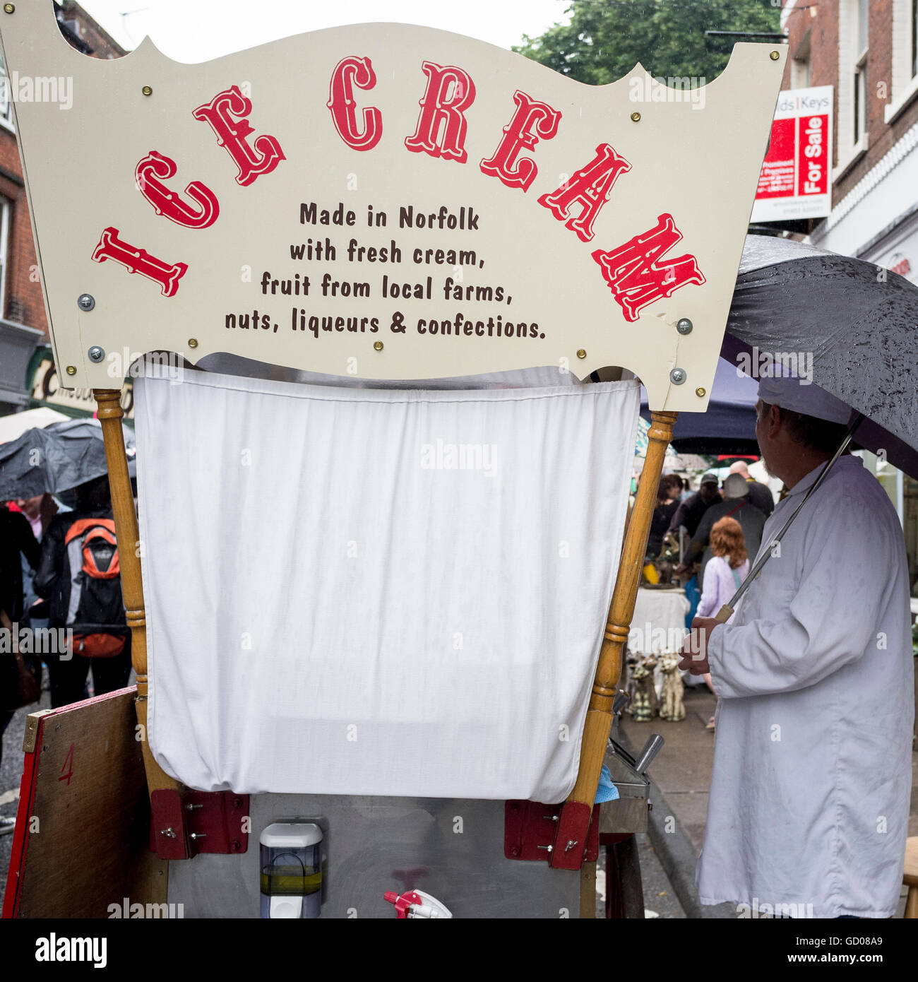 Ice cream man with his umbrella up at the 2012 Norwich Lanes Summer Fayre - Stock Image