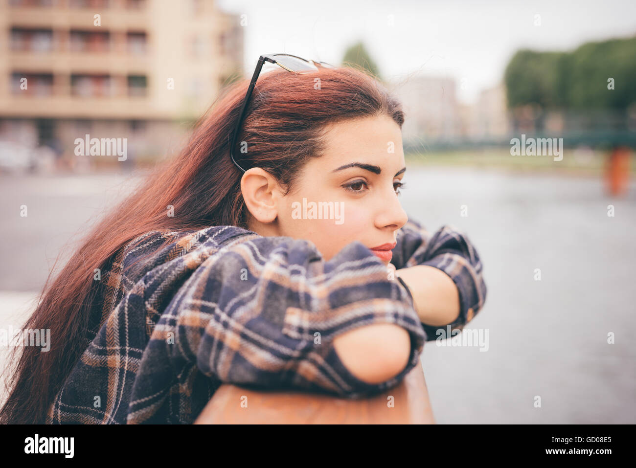 Half length of a young beautiful reddish brown hair caucasian girl leaning against a windowsill overlooking - pensive, - Stock Image