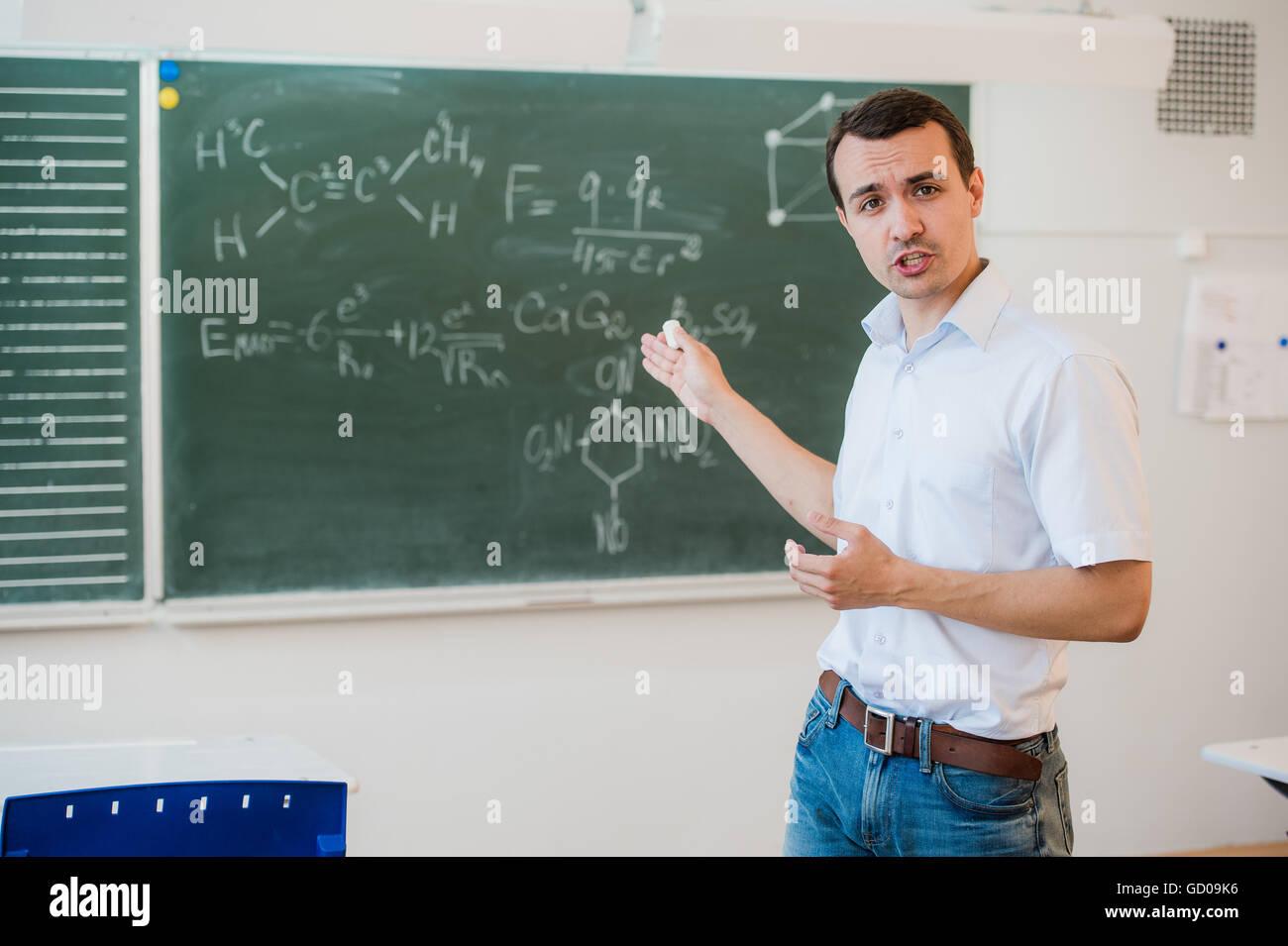 Young teacher near chalkboard in school classroom talking to class - Stock Image