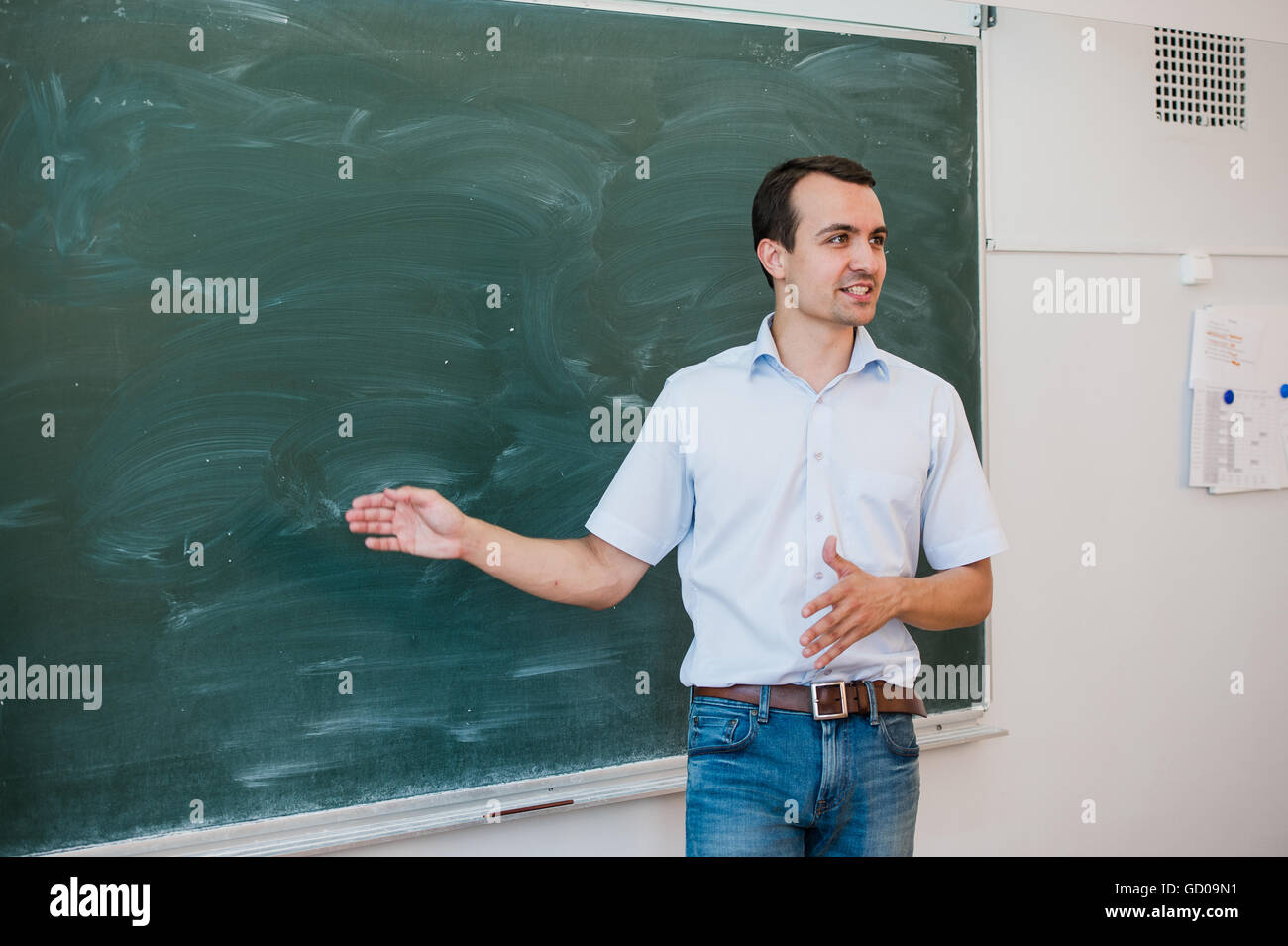 Portrait of young handsome student or teacher in a class pointing at blank chalkboard, talking and smiling - Stock Image